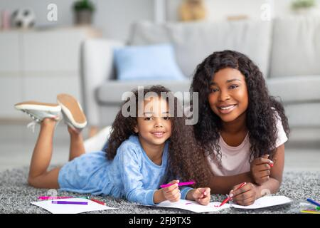 Positive black mom and her happy daughter drawing together on floor at home. Parent child pastimes concept - Stock Photo