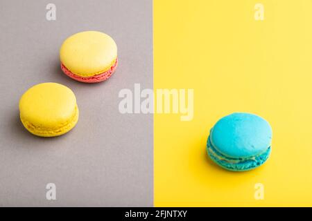 Yellow and blue macaroons on trendy gray and yellow background. side view, copy space, close up, still life. Minimalism, morning, contrast concept.