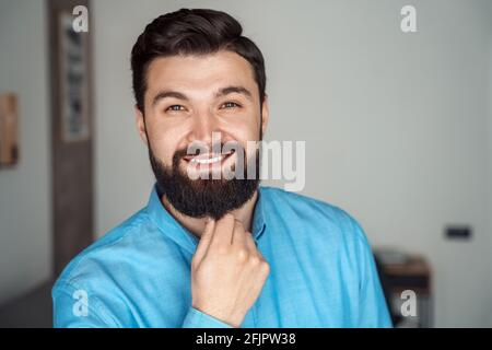 Headshot portrait of successful startup manager looking at camera touching beard