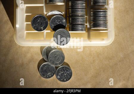 One Yen on the coin box, in shallow focus. Saving money concept, cash management