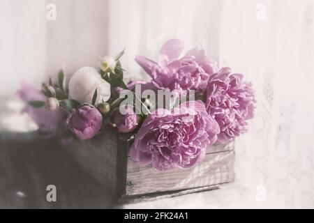 Romantic vintage pink peonies in an old wooden textured box. copy space.