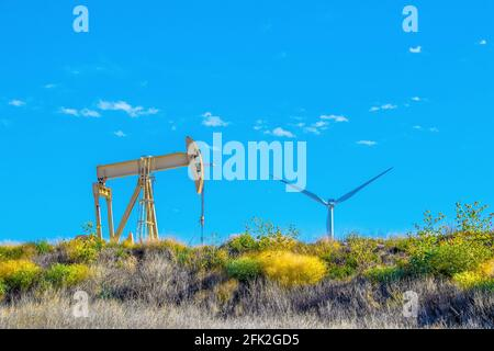 Yellow oil well pump jack sitting on ridge with colorful flowers and folliage with giant industrial windmill peeping over the horizon against beautifu