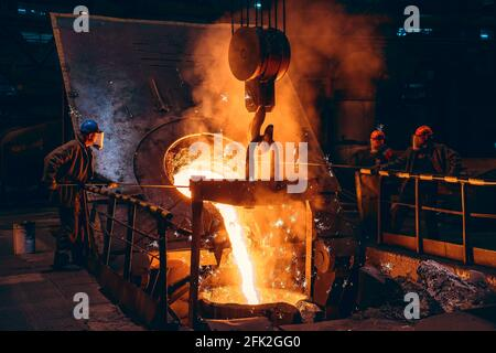 Pouring bright liquid iron or metal with sparks into container in steel mill or workshop blast furnace foundry. Metal casting process in metallurgical plant.