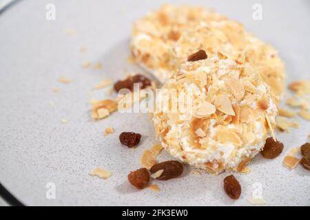 Close up of delicious dietary sweet cheesecakes sprinkled with raisins and nuts. Concept of appetizing cheesecakes with delicious filling home cooking.