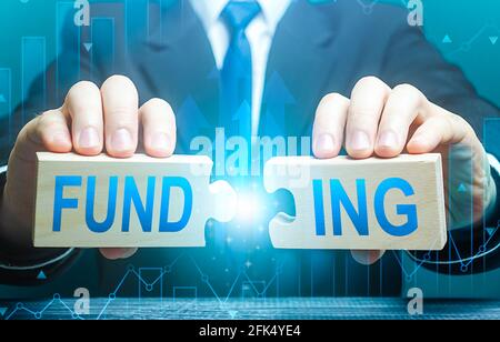 Businessman connects puzzles with the word funding. Investing in a business project, raising funds. Providing financial resources. Credit, donations,