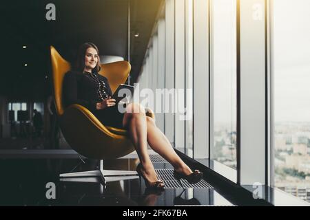Portrait of a charming adult plus-size caucasian businesswoman sitting on an orange armchair with a digital tablet in her hands and looking outside th