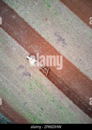 Tractor ploughing in field aerial view with agricultural crop patterns, Victoria, Australia.