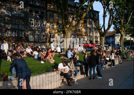 13.06.2018, Porto, Portugal, Europe - People meet at a popular spot for locals around a narrow stretch of lawn under shady trees in the old town.