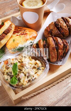 Disposable tableware, lemon tea, slate, mouth-watering sausage rolls and dill and baked potatoes with meat on a wooden tray. Place for text. Street fo