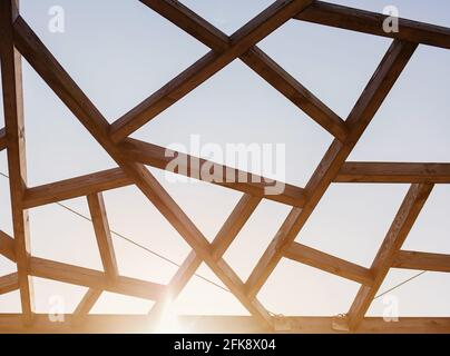 Roofing construction. Wooden roof frame house construction. Abstract structure background. Wood texture pattern with sunbeam