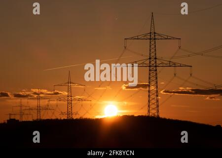 Electricity pylons with evening sun in the background.