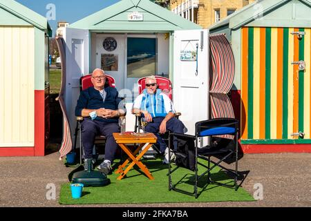Two Local Men Enjoying The Sunshine Outside A Beach Hut On Hove Seafront, Brighton, East Sussex, UK.