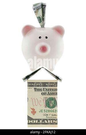 American 100 dollar currency in pink piggy bank standing on house made of U.S. money isolated on white ideally representing home savings, loans, real