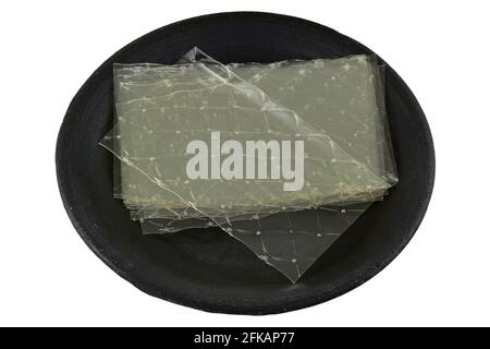 Sheets of Gelatin leaves on a dark ceramic plate, isolated on white