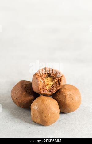 Healthy energy raw balls and protein powder in measuring scoop on light grey table. Handmade pp sugar free sweeties with cocoa for sportsmen. Fitness - Stock Photo