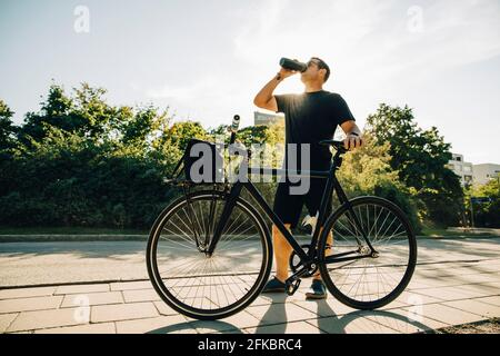 Sportsman drinking water while standing on footpath against sky on sunny day