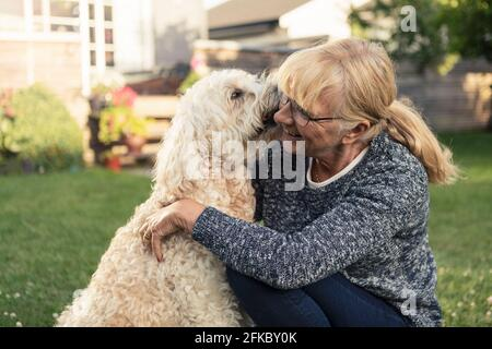 Dog kissing blond woman in front yard