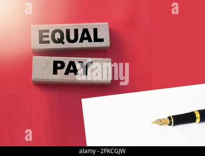 Equal pay words on wooden blocks. Income differences between men and women concept.