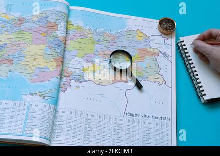 Turkey map on a book, Taking notes to a road trip preparations. A magnifying glass and a compass left side of the page. Stock Photo