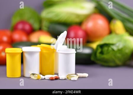Bottles with food nutrition supplement pills in front of fruits and vegetables in background - Stock Photo