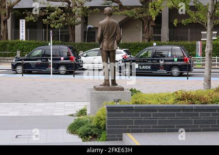 Statue of Olympics-founder Pierre de Coubertin at Japan Olympic Museum. On the road are taxis with Tokyo Paralympic logos on them. (4/2021)