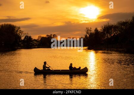 Silhouette of couple with dog kayaking in the lake at sunset