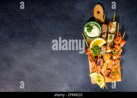 Assortment various barbecue Mediterranean grill food - fish, shrimp, crab, mussels, kebabs with sauces, black concrete background, above copy space