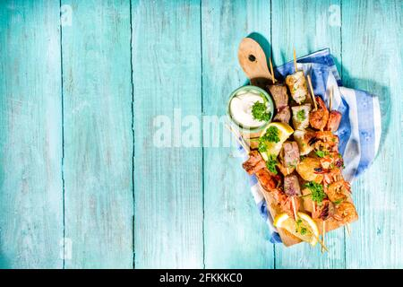 Assortment various barbecue Mediterranean grill food - fish, shrimp, crab, mussels, kebabs with sauces, light blue sunne wooden background