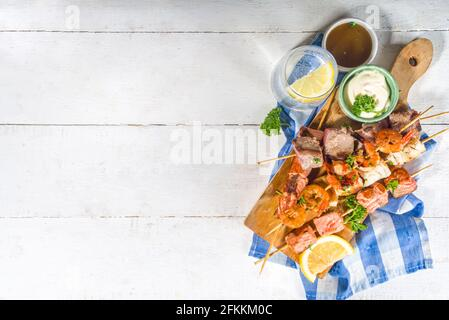 Assortment various barbecue Mediterranean grill food - fish, shrimp, crab, mussels, kebabs with sauces, white wooden background, above copy space