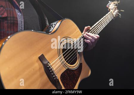 Classical acoustic guitar in the hands of a musician copy space.