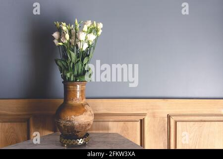 Retro style room. Clay old vase with white flowers roses on the background of a gray empty wall. Vintage interior of an old house living room. Old fashioned decor and interior design. High quality photo