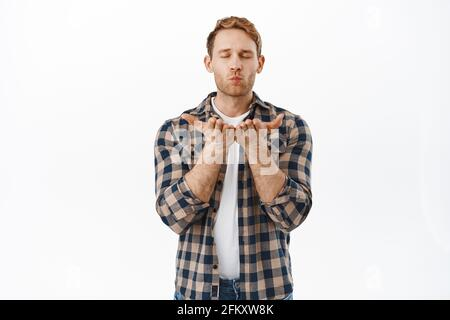 Passionate redhead man sending a kiss, blowing at open hands as blowing mwah at camera, standing romantic against white background