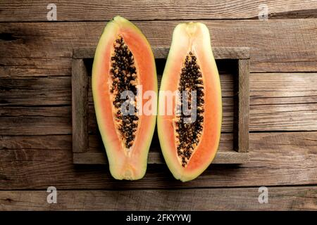 Fresh tropical papaya fruit in a wooden delivery box on a wooden background flat lay top view with copy space for some advertisement text
