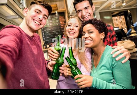 Multiracial friends taking selfie and drinking beer at fancy brewery restaurant - Friendship concept with young people enjoying time together
