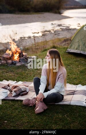 Rest near mountains. Young girl in the afternoon sits near a tent and enjoys mountain views. The campfire is lit on the side.