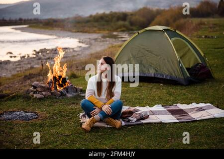 Front view of young brunette in the afternoon sits near a tent and enjoys mountain views. The campfire is lit on the side. Camping and hiking in the m