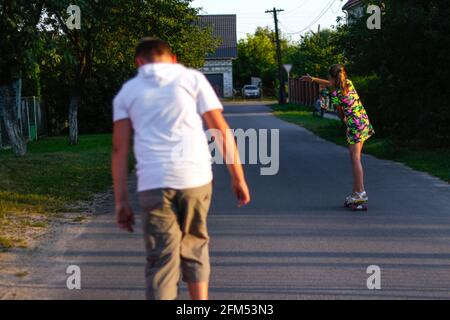 Defocus happy young girl and boy playing on skateboard in the street. She put arms out to the sides Caucasian kids riding penny board, practicing