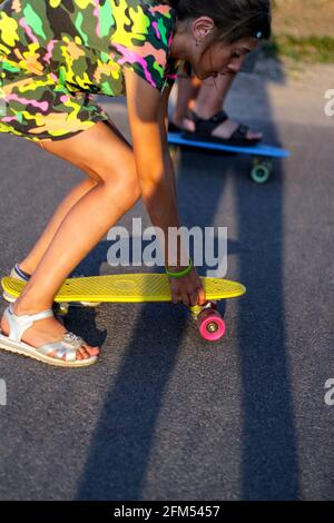 Defocus happy young girl and boy playing on skateboard in the street. Caucasian kids riding penny board, practicing skateboard. Friendship concept