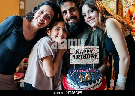 Portrait of a Latino family celebrating little girl's 10th birthday