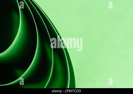 Abstract colored macro background, created with curved green paper sheets. Curved lines and shapes and soft vivid colors.