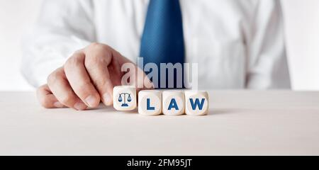 Businessman placing the wooden cubes with the word law. Business legislation or legal rules concept.