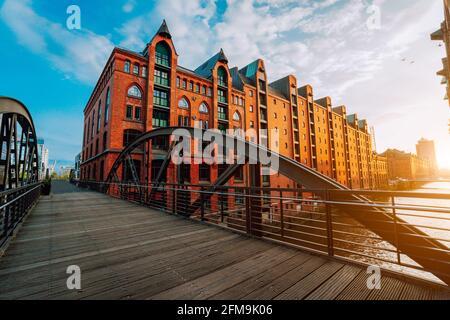 Arch bridge over canals in the Speicherstadt of Hamburg. Warm evening sun light on red brick building.