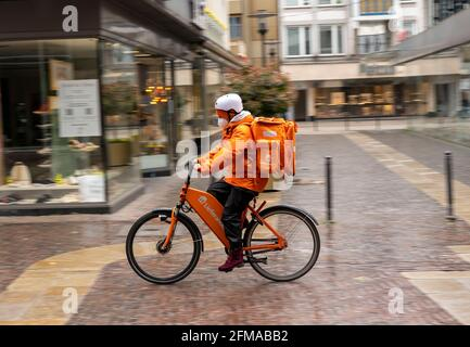 Delivery service Lieferando.de, delivery messenger with companies bicycle in the city centre, Rathenaustrasse, in Essen, NRW Germany,