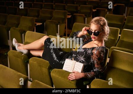 Retro style young blonde woman in movie theater