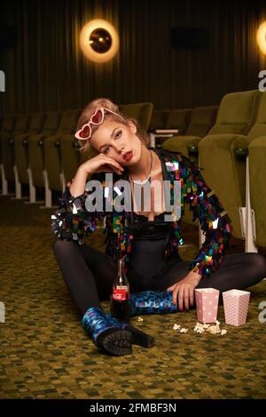 Retro style young blonde woman with popcorn in movie theater