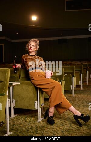 Retro style young blonde woman with coke bottle in cinema room