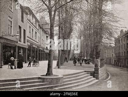 A late 19th Century view of The Pantiles, a Georgian colonnade in the town of Royal Tunbridge Wells, Kent, England constructed in the first part of the 18th century. Formerly known as The Walks and the (Royal) Parade, it leads from the well that gave the town its name. The pantiles used to pave the Upper Walks should not be confused with roofing pantiles. The paving installed there comprised one-inch thick square tiles made from heavy wealden clay, so named because they were shaped in a wooden pan before firing.