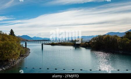 Panorama view of Lake Tekapo with the Southern Alps in the background and people walking on the Footbridge, South Island