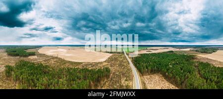 Aerial View Of Highway Road Through Deforestation Area Landscape. Green Pine Forest In Deforestation Zone. Top View Of Field And Forest Landscape