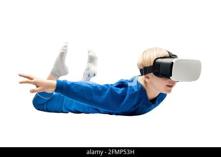 Little boy flies in virtual reality glasses on white background. Video games concept.